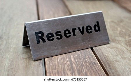 Reserved Table. A tag of reservation placed on the wood table. Reserved logo. Reservation sign. Metal tag with reservation logo. Reserved table in a restaurant. Hungry.