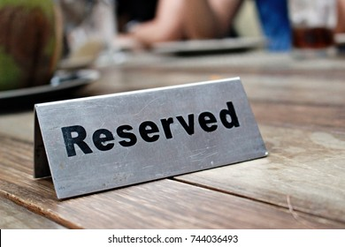 Reserved Table. A tag of reservation placed on the wood table. Reserved logo. Reservation sign. Metal tag with reservation logo. Party. hang out. friend meeting.