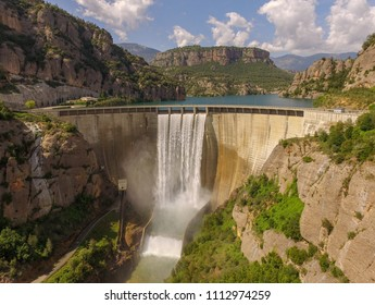 Reservoir and dam overflowing, Llosa del Cavall 2018 (Lleida Pyrenees Mountains, Catalonia, Europe). Void. Shock absorber, height engineering. Waterfall and rainbow.