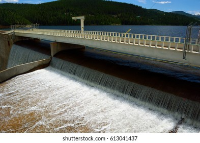 Reservoir Dam Spillway with Water Pouring over the Top in the Mountains