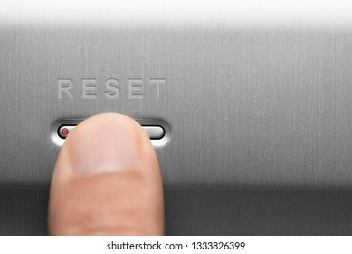 The reset button on the aluminum panel. Male finger