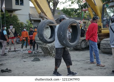 A resident carrying car tires taken from car burried arter liquefaction of land in Petobo Palu Central of Sulawesi on 12nd october 2018