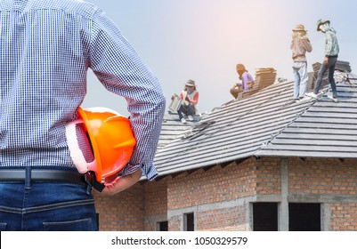 resident engineer holding yellow safety helmet at new home building under construction site with  workers installing concrete tiles on the roof while roofing house residential development concept