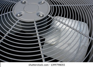Residential air conditioning unit outdoors with fan and coils