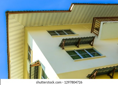 Residential apartment building on sunny day with blue sky.