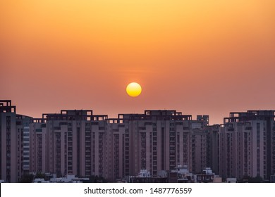 Residential apartment building and plot houses exterior view during sunset over an urban cityscape in the evening at Gurugram, Haryana, India.
