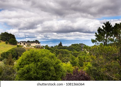 Residential areas with houses scattered on hills; Santa Cruz mountains on a cloudy day, Saratoga, south San Francisco bay area, California