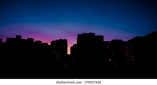 Residential Areas at Night. Stepped silhouette skyscrapers on a background of red and blue sky