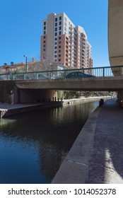 Residential building and elevated apt light rail guide way alongside Mandalay Canal Walk in Las Colinas, Irving, Texas. Winding canal walkway along tree-lined path, peaceful, stirring Old World style