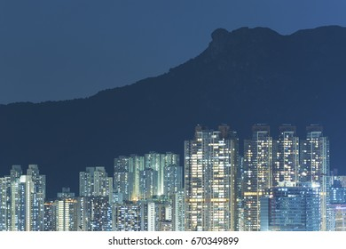 residential building under lion rock in Hong Kong city at night