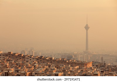 Residential buildings in front of Milad Tower in air-polluted skyline of Tehran illuminated with golden sunset.