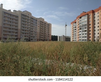 Residential buildings at high grass and cloud background (deadpan style)