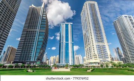 Residential buildings in Jumeirah Lake Towers timelapse in Dubai, UAE.  The JLT is a large development which consists of 79 towers with 3 artificial lakes and park. View with blue cloudy sky from park