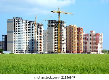 Residential buildings, some of them under construction, with beautiful green field foreground
