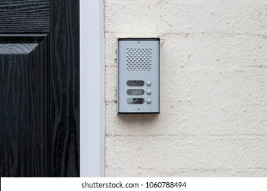 residential buzzer intercom next to a black door on a white wall