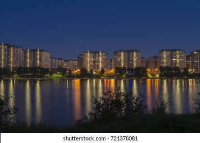 Residential complex of skyscrapers and the waterfront across the river reflected in the water. Night cityscape
