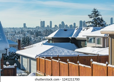 Residential driveway with cityscape on horizon in winter time. Cityscape on bright sunny winter day in Canada