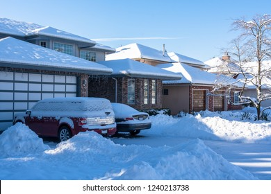 Residential driveway and front yard of houses in snow on winter season