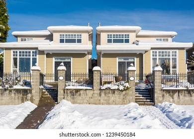 Residential duplex house with front yard in snow. North American family duplex house on winter sunny day