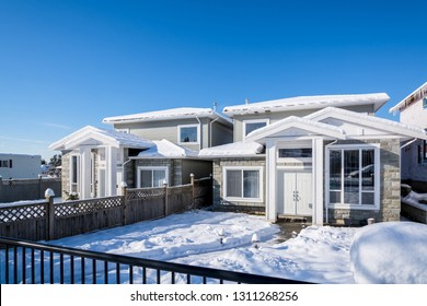 Residential duplex house with front yard in snow. North American family duplex house on bright winter day