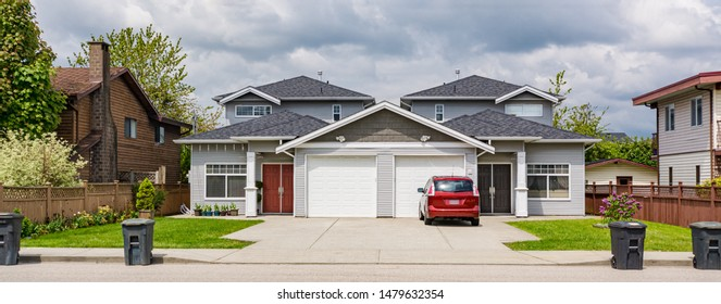 Residential duplex townhouse with red car parked on concret driveway