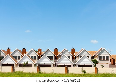 Residential fenced house complex against blue sky.
