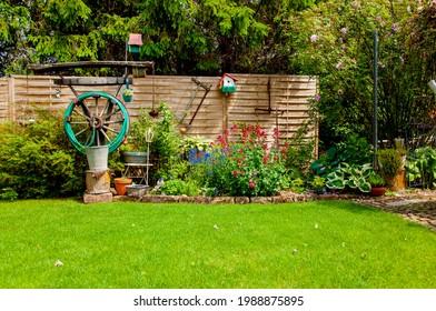 Residential Garden, private garden. Landscape design in home garden, beautiful landscaping in backyard in spring. Beautiful home garden in full bloom. Beautiful landscaping in Backyard with flowerbed.