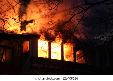 residential home on fire, fully involved, engulfed in orange fire and flames