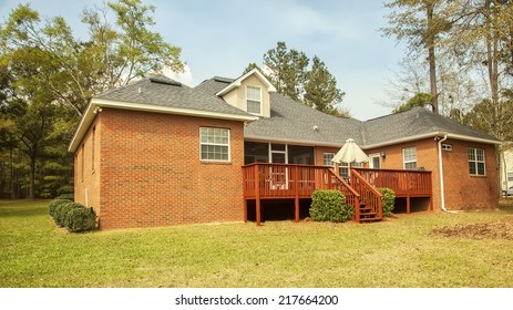 Residential house with backyard deck and large yard.