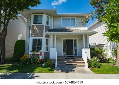 Residential house with concrete pathway in front for sale on bright sunny bright day