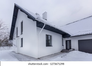 Residential house on winter cloudy day. White house in snow