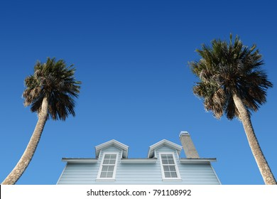 Residential house with palm trees on blue sky background