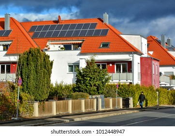Residential house with solar panels on a red tile roof. Rural landscape. German Countryside. Accommodation. Fenced yard with a garden. Life in a town. Germany, Zorneding - November 19, 2017