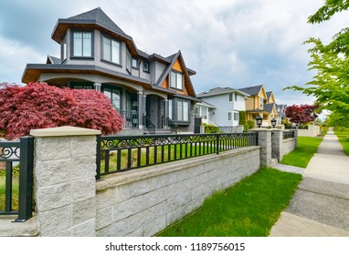 Residential houses with concrete pathway along the front yard. Metal fence in front of residential house