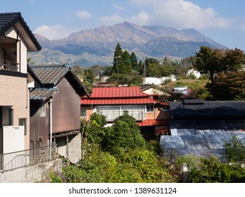 Residential houses in Minamiaso village with Aso volcanic peaks at the distance - Aso-Kuju National Park, Kumamoto Prefecture, Japan