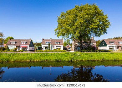 Residential houses at a small touristic landmark village with a canal and reflection at the village Oranje in the center of province Drenthe, the Netherlands.