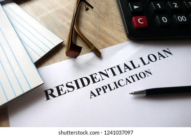 Residential loan application with pen, calculator and glasses on desk