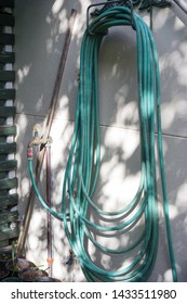 residential long green hosepipe or garden hose hanging up on a metallic steel decorative fitted bracket attached to a wall of a house and an outdoor tap stowed away for neatness and to be tidy