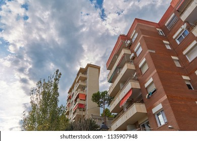 Residential multi-storey building of red brick in cloudy weather in Calella, Spain.