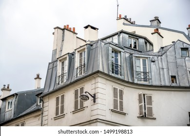 Residential multi-storey stone house with wooden shutters and apartments in the attic with metal sheathed windows and roof chimneys located on one of the streets of old Paris with old buildings