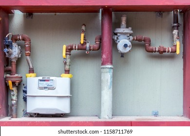 Residential natural gas meters and red plumbing on exterior wall to measure household energy consumption. Gas meter in Turkey