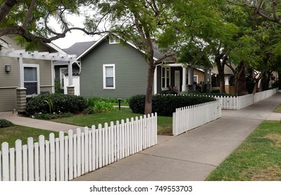 Residential neighborhood homes, picket fence, trees and sidewalk. Nobody.