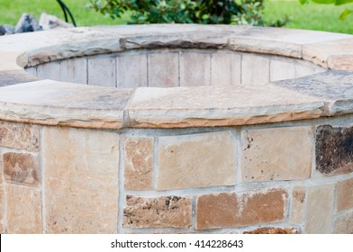 Residential outdoor stone firepit on concrete patio close-up.