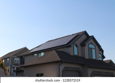 Residential solar installation with black solar panels. Low profile photovoltaic system on suburban home.