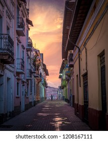 A residential street in Old Town Quito, Ecuador at dusk after a heavy rain storm. The sky is lit with orange and yellow as lone figure walks the cobbled street. Puddles reflect the colour of the sky.
