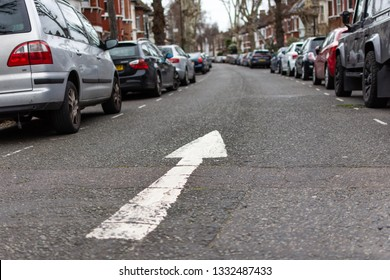 A residential street where parked cars line the sides of the street. The angle is low and there is a white arrow painted onto the road, pointing forward, indicating a one way road.