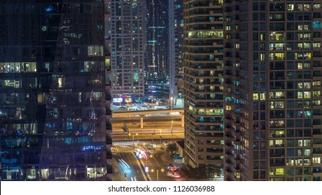 Residential towers with lighting and illumination timelapse. Road and promenade on Dubai Marina and JLT skyline at night. Traffic near skyscrapers with glowing windows