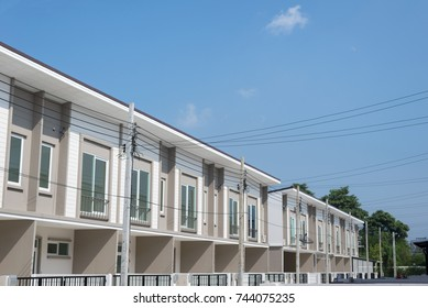 Residential townhomes, townhome with electric wire, cables and clear blue sky