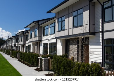 Residential townhouses on blue sky background on sunny day. External facade of a row of colorful modern urban townhouses.brand new houses just after construction on real estate market