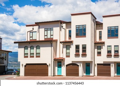 Residential townhouses with scenery view on a lake and mountains. Townhomes with wide garage door and cars parked in front. Residential townhouses on blue sky background on sunny day